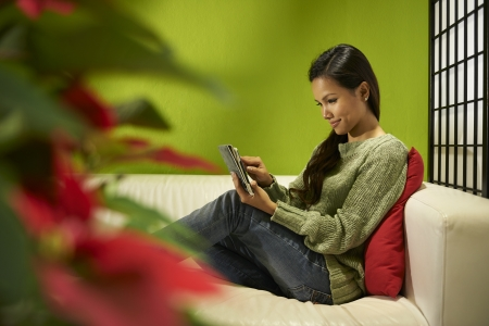 Young people and technology, Asian girl typing on digital tablet, pretty female student using computer and sitting on sofa at home photo