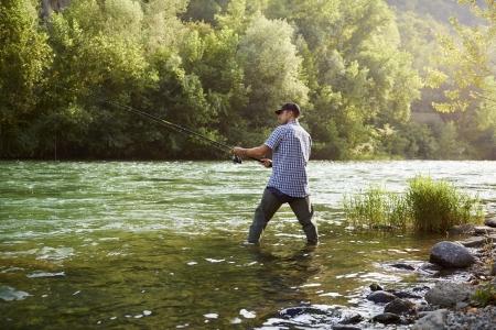 hombre de mediana edad en días festivos en el río, relajante y pesca de la trucha