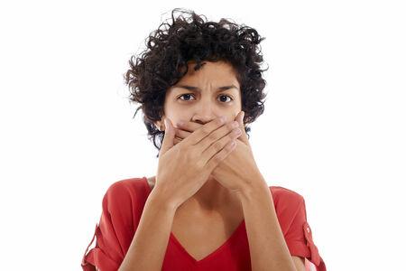 mouth closed: mujer hispana con las manos cubriendo la boca, sin palabras y enojado, mirando a la c�mara Foto de archivo