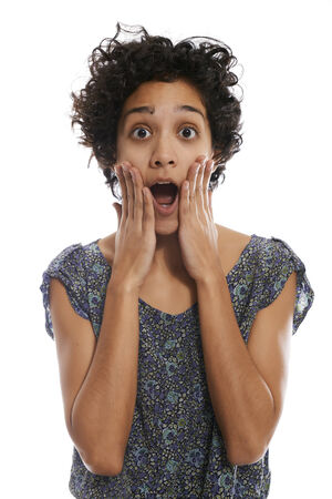 portrait of shocked hispanic girl with mouth open and hands on face, looking at camera on white background photo