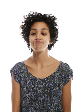 hispanic woman doing facial expression and touching nose with tongue on white background photo