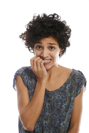 portrait of worried and stressed hispanic girl biting nails and looking at camera on white background  photo