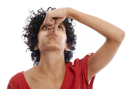 snuff: hispanic woman holding breath closing nose with fingers on white background