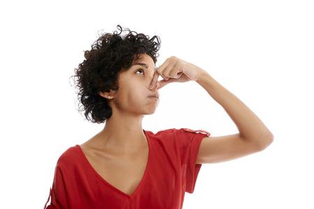 mujer hispana contención de la respiración cerrando la nariz con los dedos en el fondo blanco