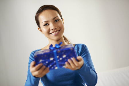 asian woman showing present to the camera and smiling. Copy space photo