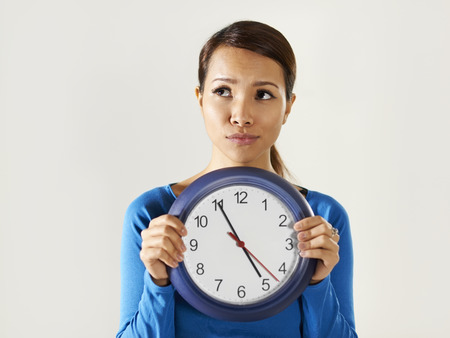 portrait of asian business woman holding big blue watch and looking away with worried expression. Copy space photo