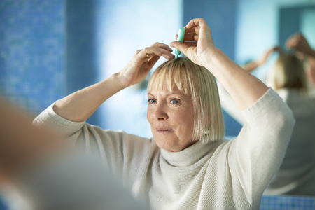 old caucasian woman applying lotion to prevent hair loss, looking at mirror in bathroom photo