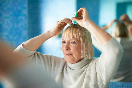 vieja mujer caucásica de aplicar la loción para evitar la caída del cabello, que mira el espejo en el baño