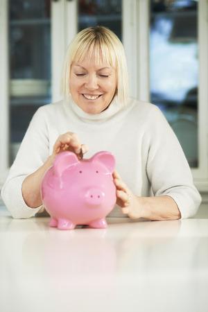portrait of happy caucasian senior woman saving euro coin into piggybank and smiling photo