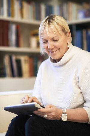 portrait of beautiful old woman using tablet pc and smiling, sitting on sofa at home photo
