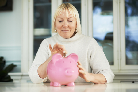 portrait of happy caucasian senior woman saving euro coin into piggybank and smiling Stock Photo - 27721811