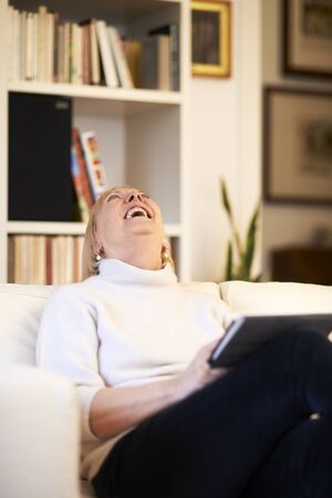 portrait of beautiful old woman using tablet pc and smiling, sitting on sofa at home Stock Photo - 27721818