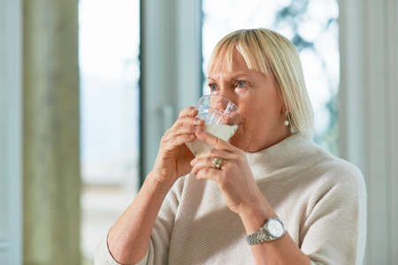 Portrait of senior caucasian woman drinking fresh milk for breakfast at home photo