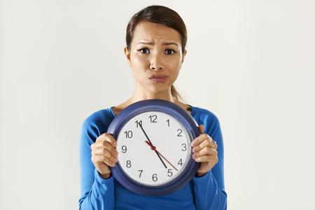 portrait of asian business woman holding big blue watch and looking at camera with worried expression photo