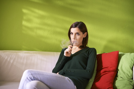 young female smoker smoking e-cigarette at home, sitting on sofa and relaxing photo