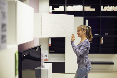 young hispanic woman shopping for furniture, sofa and home decor in store