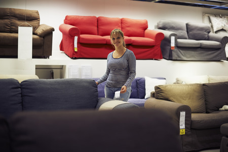young hispanic woman shopping for furniture, sofa and home decor in store, looking at camera and smiling