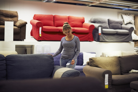 buy: young hispanic woman shopping for furniture, sofa and home decor in store
