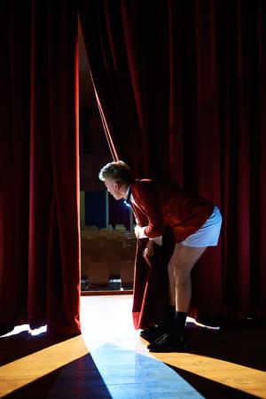 Kunst und Unterhaltung im Theater mit lustigen Mann arbeitet als Moderator, stand mit Hose hinter die Kulissen und Blick auf Grube