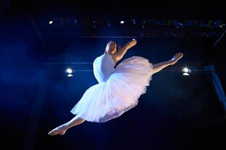 Artes y entretenimiento en el teatro con la bailarina clásica femenina en tutú, salto de altura en el escenario durante la actuación