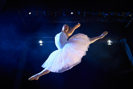 Arts and entertainment in theatre with female classic dancer in tutu, jumping high on stage during performance photo