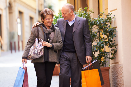 an elderly couple: Happy people with senior man and woman shopping and walking with bags in italian city street