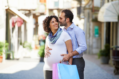 kissing pregnant belly: Portrait of happy people with husband and pregnant wife shopping and having fun in italian city street