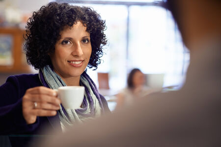 People in cafeteria with woman drinking espresso coffee and holding cup photo