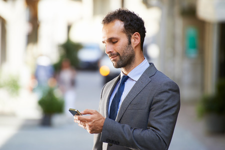 都市通りでテキスト メッセージを入力して携帯電話上の実業家との幸せな人々
