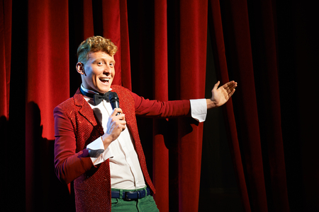 showman: Arts and entertainment in theatre with funny man working as anchorman, standing against red curtains with microphone