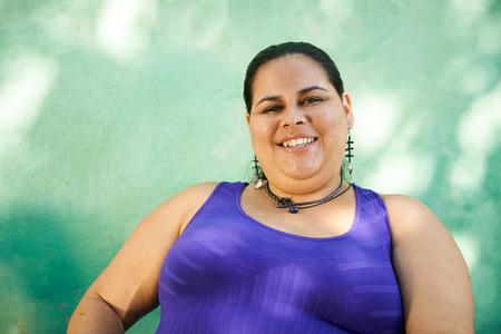 mujer fea: Retrato de mujer hispana con sobrepeso mirando a la cámara y sonriendo Foto de archivo