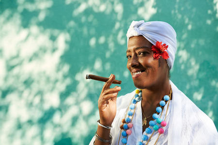 Portrait of african cuban woman smoking cohiba cigar and looking at camera smiling  Stock Photo