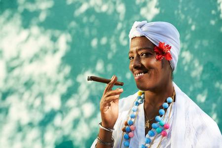 Retrato de la mujer cubana africano fumando cigarros Cohiba y mirando a la cámara sonriendo