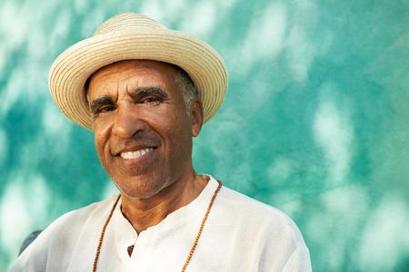 Portrait de la retraite homme hispanique senior avec chapeau de paille assis dans le parc et regardant la caméra avec l'heureuse expression