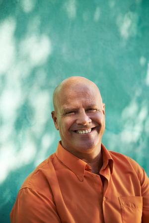 bald man: Retrato del hombre caucásico maduro con camisa naranja sentada en el parque y mirando a la cámara con expresión feliz