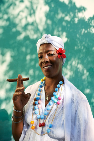 Portrait of african cuban woman smoking cohiba cigar and looking at camera smiling  photo
