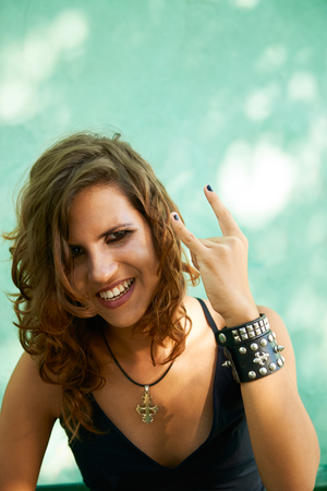 rebel: Portrait of young female rocker gesturing with hands and looking at camera against green wall  Stock Photo