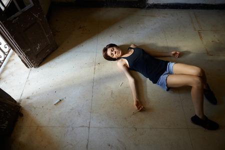 Hohe Winkel Ansicht der jungen Mädchen in Überdosis Heroin halten Spritze und auf dem Bürgersteig liegend Standard-Bild - 29384625