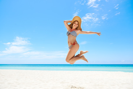 Portrait of young beautiful girl at tropical beach for vacations, jumping mid-air for joy, looking at camera and smiling. Copy space photo