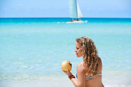 Portrait of young beautiful girl at tropical beach for vacations in Varadero, Cuba, drinking cocktail in coconut and sitting on sand photo