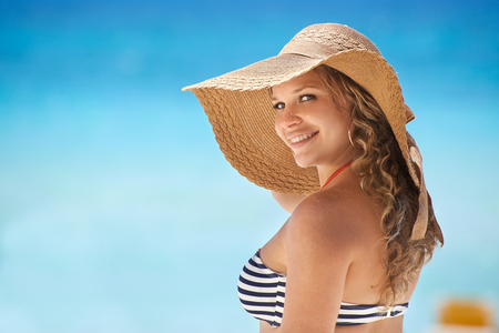 Portrait of young beautiful girl at tropical beach in Cuba for vacations, looking at camera and smiling. Copy space on sea photo