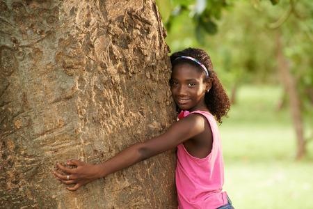 black girl: Ökologie und Umwelt-Porträt der jungen African American Mädchen umarmen und umarmt Baum im Park, lächelnd und auf Kamera