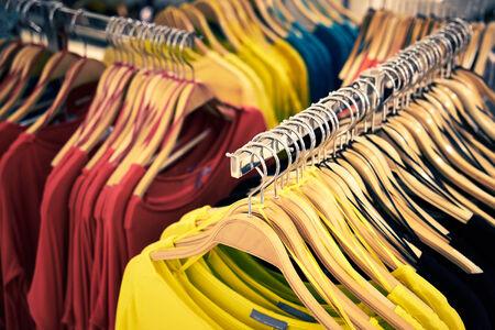 ahorcada: Ropa y tienda al por menor: Vista de la tienda de ropa con la camiseta colgada en el stand Foto de archivo
