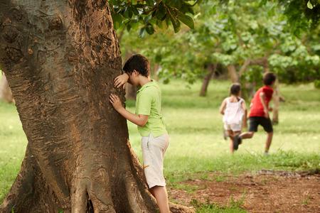 niños y niñas jugando a las escondidas en el parque, con el cabrito que el conteo se inclina en árbol