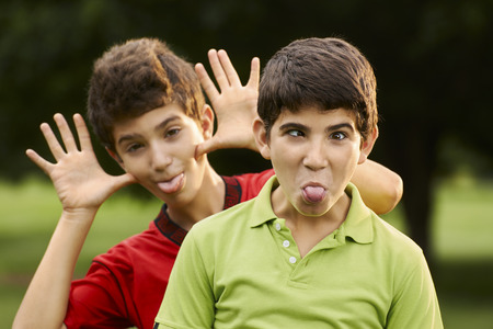 Portrait of happy hispanic children, two brothers, making a face and grimacing at camera outdoors in park photo