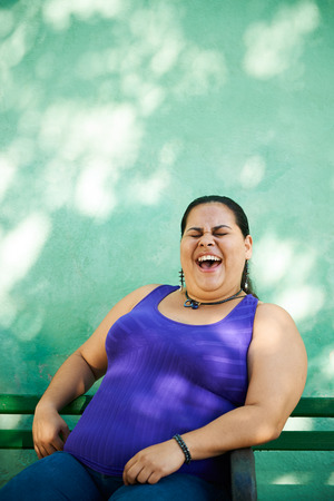 Portrait of overweight hispanic woman looking at camera and smiling photo