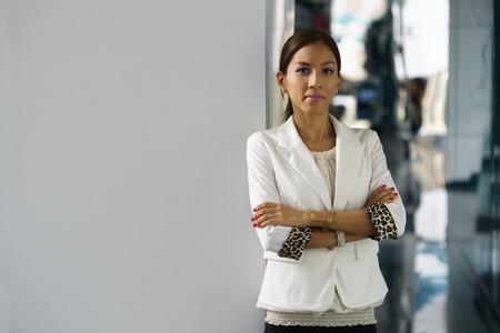腕を組んで白い壁にもたれて tailleur で幸せと自己の自信を持ってラティーナ実業家の肖像画。コピー スペース 写真素材