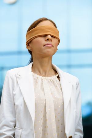 ojos vendados: Concepto de futuro y las previsiones. Retrato de la empresaria latina con los ojos vendados, cerca del edificio de oficinas Foto de archivo