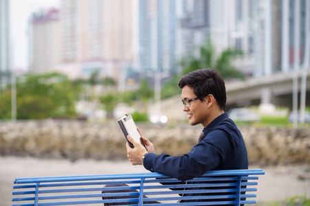 Portrait of chinese businessman sitting on bench in Panama city with skyline in background, reading emails on tablet computer Stock Photo