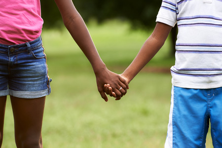 kids holding hands: People in love with african little girl and boy holding hands in park. Cropped view